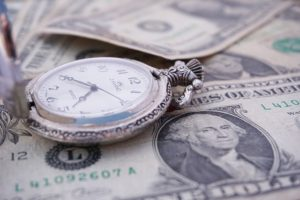 "Image of a watch with money to illustrate the ""time value of money."" This is a key point when looking at ROI vs NPV."
