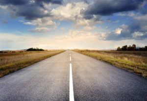 Road with clouds overhead to illustrate comparing cloud and on-premises software.